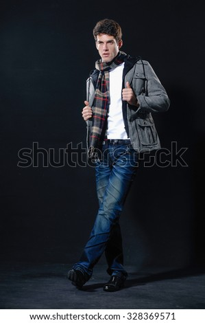 full length portrait of casual young man with scarf, walking on light background - stock photo
