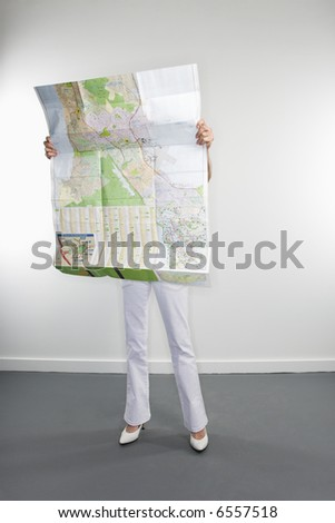Full length portrait of Caucasian woman holding map. - stock photo