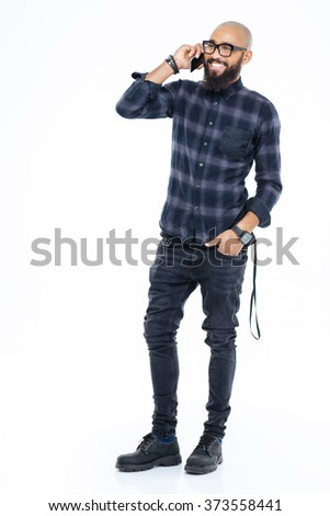 Full length portrait of cheerful african american bearded man standing and talking on mobile phone - stock photo