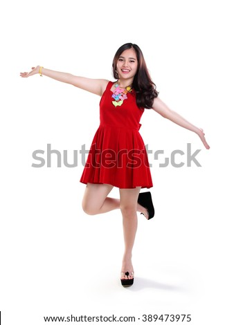 Full length portrait of cheerful Asian girl standing with arms outstretched in cute red dress, isolated on white background - stock photo