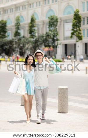 Full-length portrait of cheerful Vietnamese couple with many shopping bags - stock photo