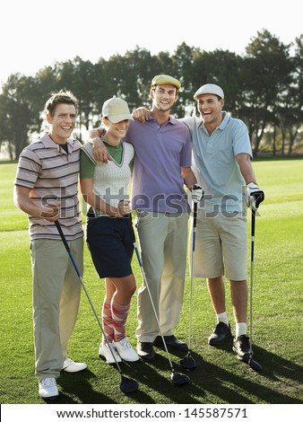 Full length portrait of cheerful young golfers on golf course - stock photo