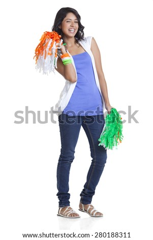 Full length portrait of cheerful young woman in casuals holding Indian tricolor pom poms over white background - stock photo