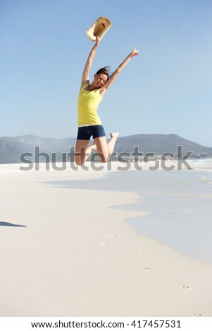 Full length portrait of cheerful young woman jumping in the air at the seashore - stock photo