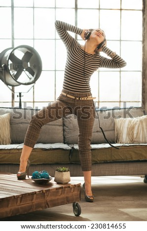 Full length portrait of cheerful young woman listening music in headphones in loft apartment - stock photo