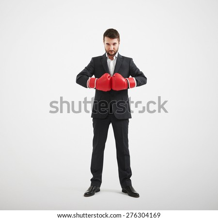 full length portrait of confided businessman in red boxing gloves looking at camera over light grey background - stock photo