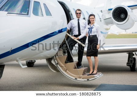 Full length portrait of confident airhostess and pilot standing on private jet's ladder at airport terminal - stock photo