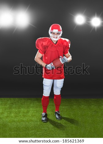 Full length portrait of confident American football player standing on field at night - stock photo