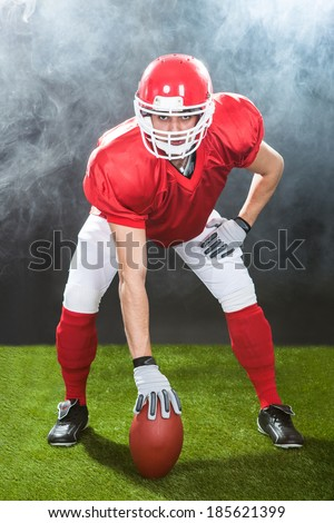 Full length portrait of confident American football snapper on field at night - stock photo