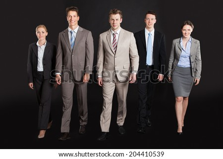 Full length portrait of confident business people walking against black background - stock photo