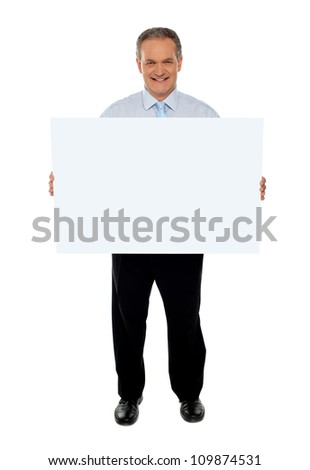 Full length portrait of confident businessman holding blank billboard isolated over white - stock photo