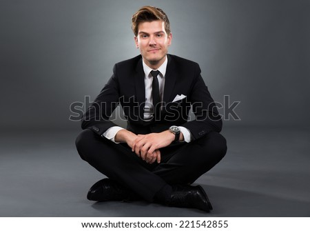 Full length portrait of confident businessman sitting isolated over gray background - stock photo