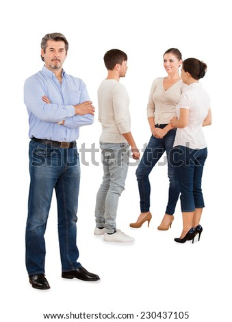 Full length portrait of confident businessman standing arms crossed with team discussing over white background - stock photo