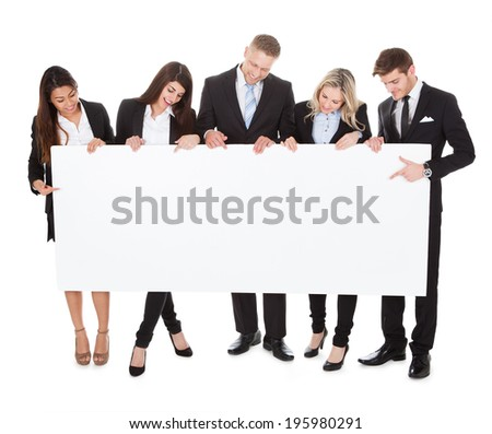 Full length portrait of confident businesspeople holding blank banner against white background - stock photo