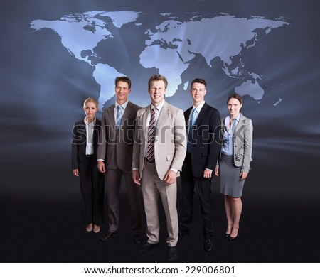 Full length portrait of confident businesspeople standing against world map. Source of reference map: http://visibleearth.nasa.gov/view.php?id=74518.