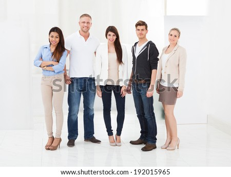 Full length portrait of confident businesspeople standing in office - stock photo