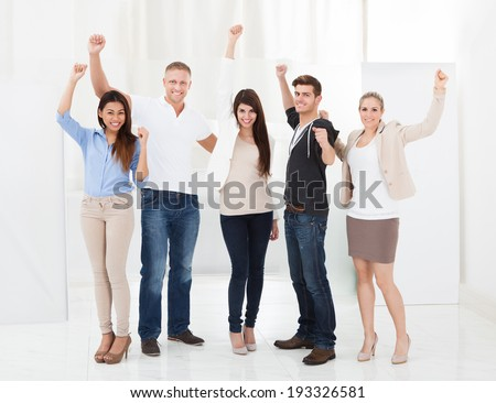 Full length portrait of confident businesspeople standing with arms raised in office
