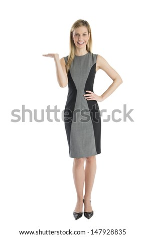 Full length portrait of confident businesswoman displaying invisible product against white background