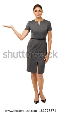Full length portrait of confident businesswoman showing invisible product over white background. Vertical shot. - stock photo