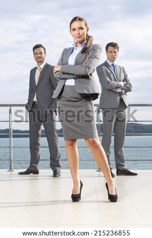 Full length portrait of confident businesswoman standing with coworkers on terrace against sky - stock photo