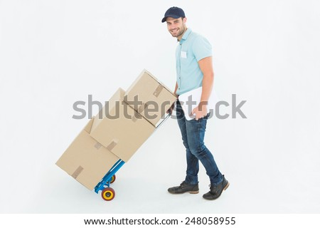 Full length portrait of confident delivery man pushing trolley of boxes on white background - stock photo