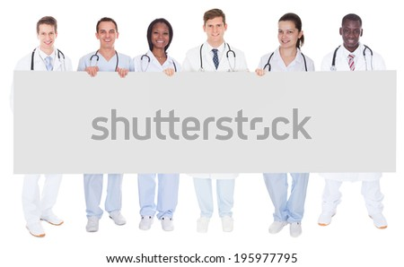 Full length portrait of confident doctors holding blank billboard over white background - stock photo