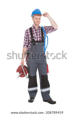 Full length portrait of confident electrician holding cable spool over white background - stock photo