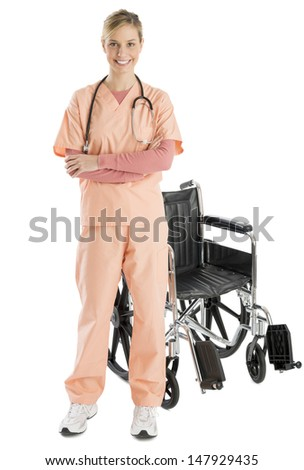 Full length portrait of confident female nurse smiling while standing by wheelchair against white background - stock photo