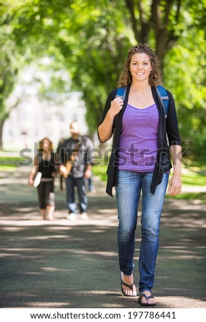 Full length portrait of confident female student with backpack walking on campus - stock photo