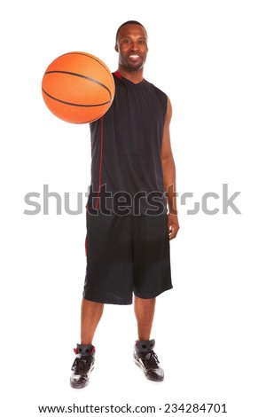 Full length portrait of confident male athlete with basketball standing over white background - stock photo