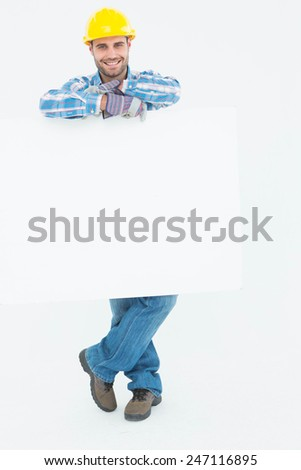 Full length portrait of confident male technicial holding blank billboard on white background - stock photo