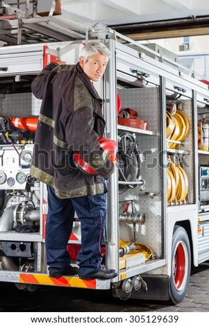 Full length portrait of confident mature fireman standing on truck at fire station - stock photo