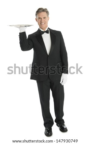 Full length portrait of confident mature waiter carrying tray while standing isolated over white background