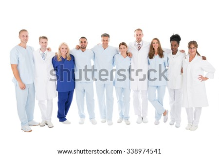 Full length portrait of confident medical team standing with arms around against white background - stock photo