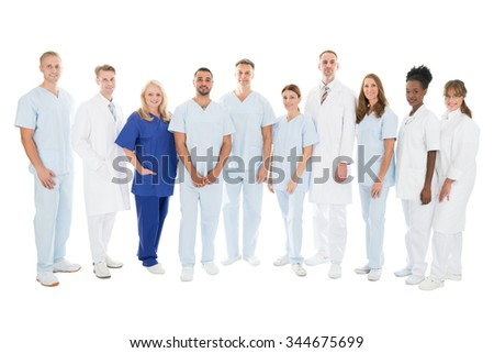 Full length portrait of confident multiethnic medical team standing in row against white background - stock photo