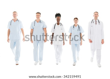 Full length portrait of confident multiethnic medical team walking in row against white background - stock photo