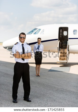 Full length portrait of confident pilot with arms crossed against stewardess and private jet at terminal
