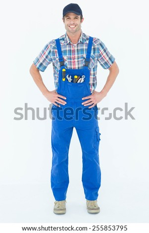Full length portrait of confident plumber with hands on hip over white background