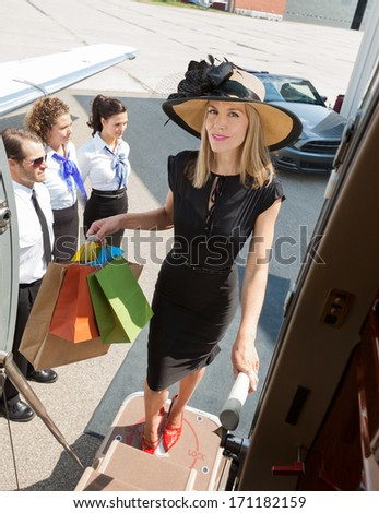Full length portrait of confident rich woman carrying shopping bags while boarding private jet with pilot and airhostess standing by at airport terminal - stock photo