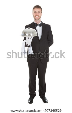 Full length portrait of confident waiter holding domed tray isolated over white background - stock photo