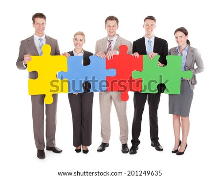 Full length portrait of confident young business people holding colorful jigsaw puzzle over white background isolated - stock photo
