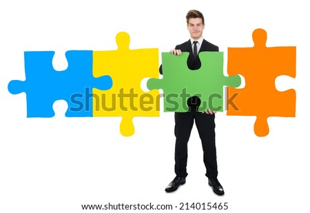 Full length portrait of confident young businessman solving jigsaw puzzle over white background - stock photo