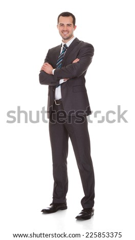 Full length portrait of confident young businessman standing arms crossed against white background