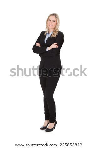 Full length portrait of confident young businesswoman standing arms crossed over white background - stock photo