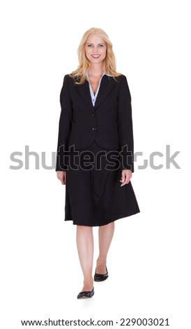 Full length portrait of confident young businesswoman walking over white background - stock photo