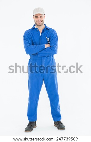 Full length portrait of confident young male mechanic standing arms crossed on white background - stock photo