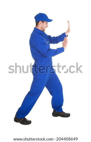 Full length portrait of confident young male worker pushing empty space isolated over white background - stock photo