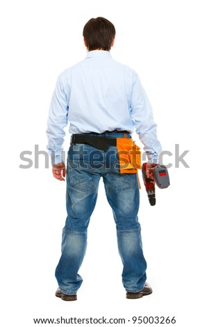Full length portrait of construction worker standing back to camera - stock photo