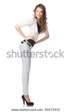 Full length portrait of coquettish female in jeans isolated on white background - stock photo