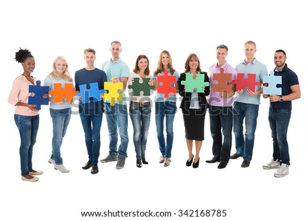 Full length portrait of creative business people holding jigsaw pieces against white background - stock photo